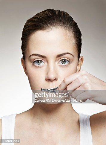 Woman zippering mouth closed : Foto de stock