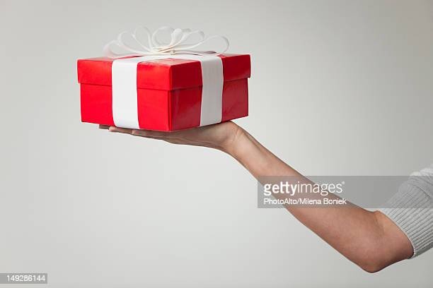 Woman's arm holding out gift box, cropped