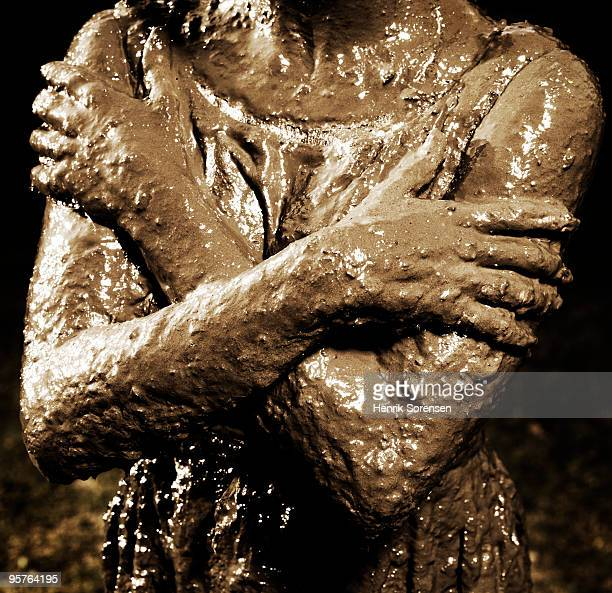 Woman?s arms and torso covered in mud portrait