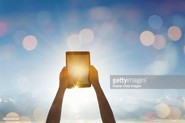 Woman's  arms pointing a tablet toward the sun