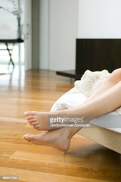 Woman's bare feet and legs dangling off end of bed