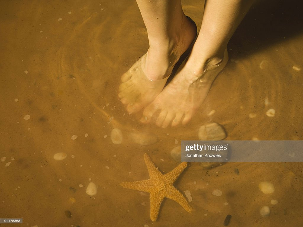 Woman�s bare feet in ocean : Stock Photo