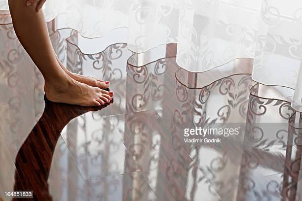 A woman's bare feet on a shiny hardwood floor