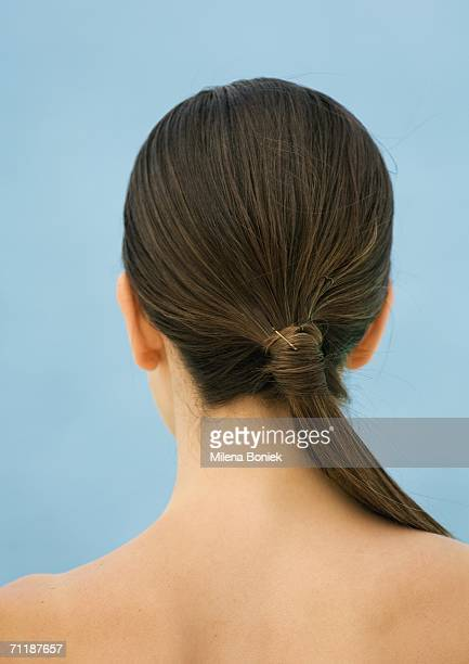 Woman's bare upper back and head with ponytail