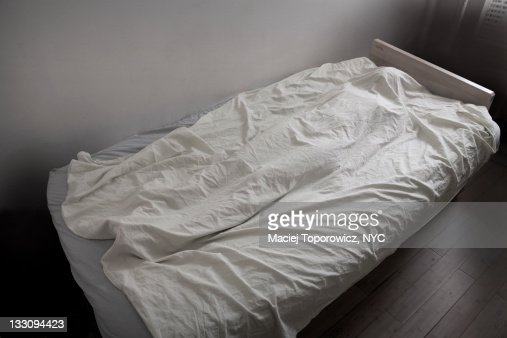 Woman's body covered with white sheet on bed.