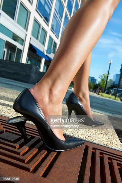 Woman's Broken High heel shoe trapped in sidewalk grate