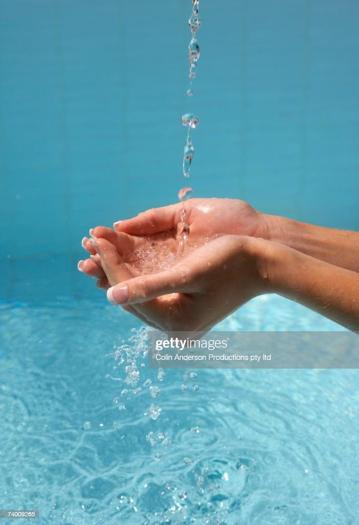 Woman's cupped hands catching water : Stock Photo