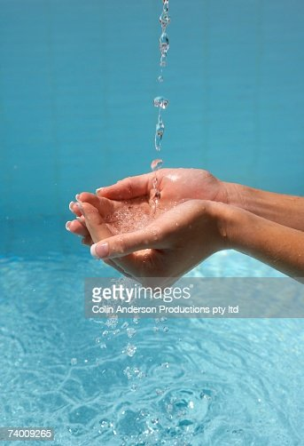 Woman's cupped hands catching water : ストックフォト