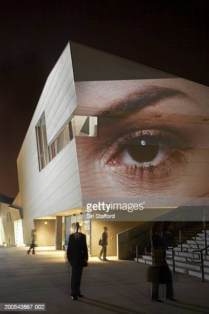 Woman's eye projected on wall of building