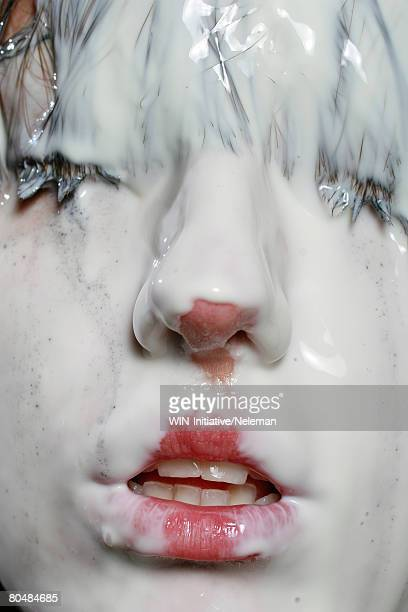 Woman's face covered with milk