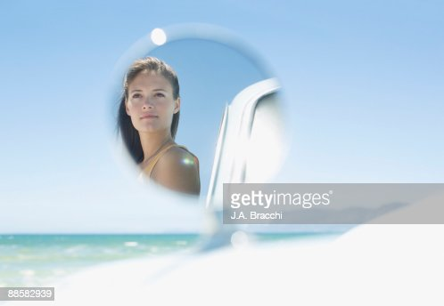 Womans face in car side view mirror at beach : Stock Photo