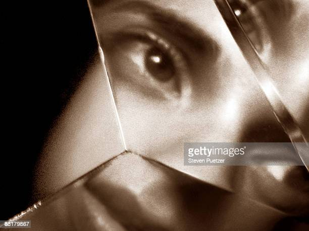 Woman's face reflected in shards of broken glass