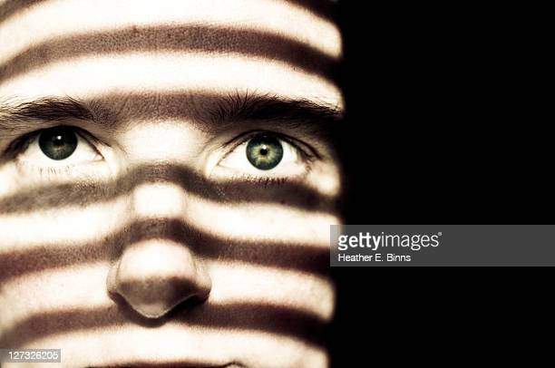 Woman's face with striped shadows
