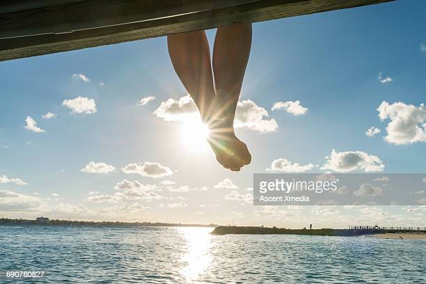 Woman's feet dangle above calm water, seaside
