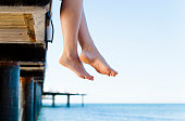 Woman's legs hanging over the edge of a wooden jetty.