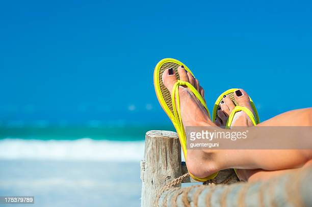 Woman's feet in yellow flip flops at the beach