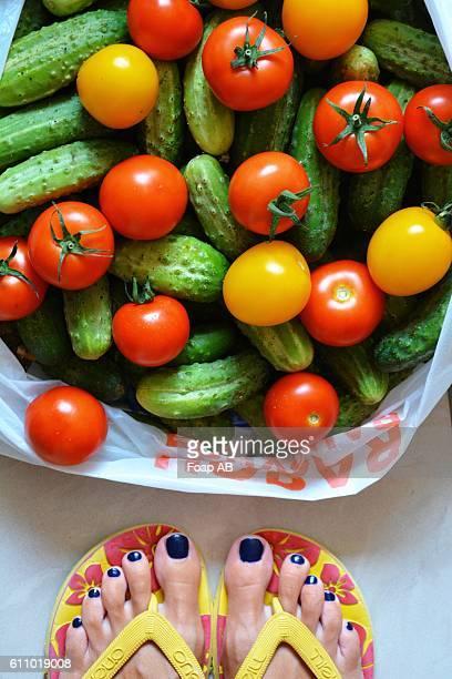 Woman's feet near the bag full of freshly cucumbers and tomatoes