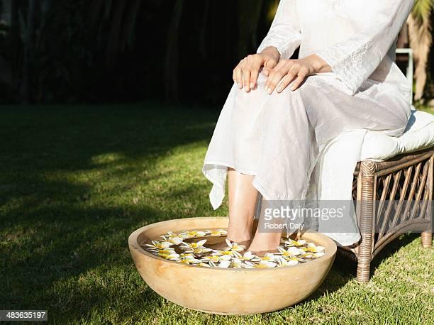 Donna ammollo i piedi in una ciotola di acqua e fiori