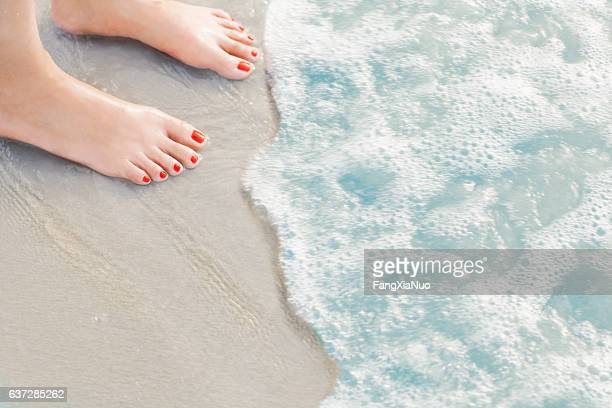 Woman's feet standing in surf at the beach