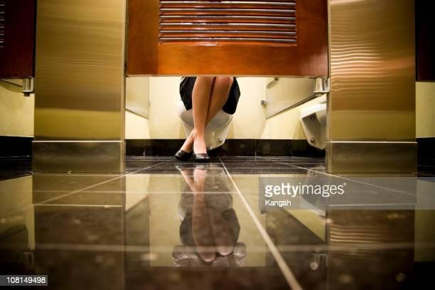 女性の足の下のトイレのブース