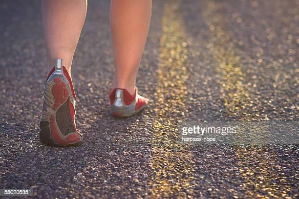 Woman's feet walking in the road