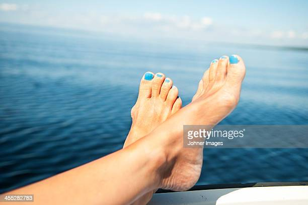 Womans feet with blue nail polish, sea in background