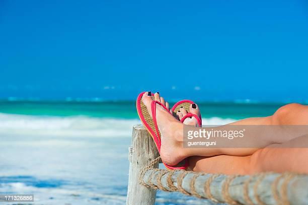 Femme pieds avec des tongs sur la plage