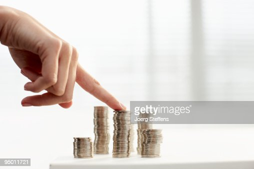 Womans finger on stack of coins : Stock Photo