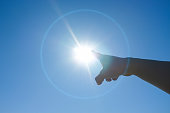 Woman's finger pointing to the sun.