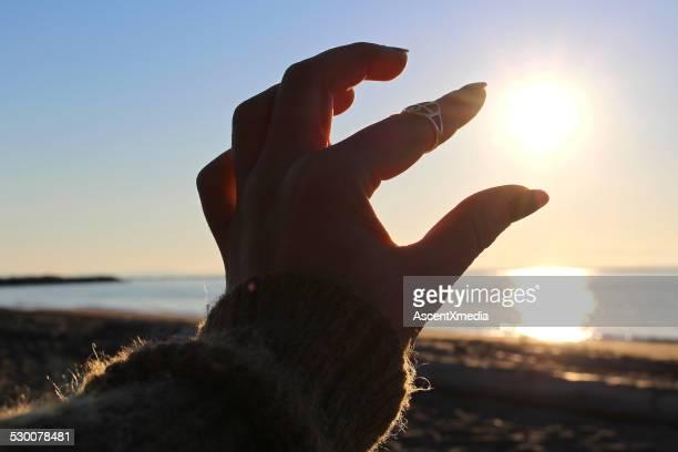 Woman's fingers capture sun above beach, sea
