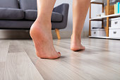 Close-up Of A Woman's Foot Walking On Heated Hardwood Floor