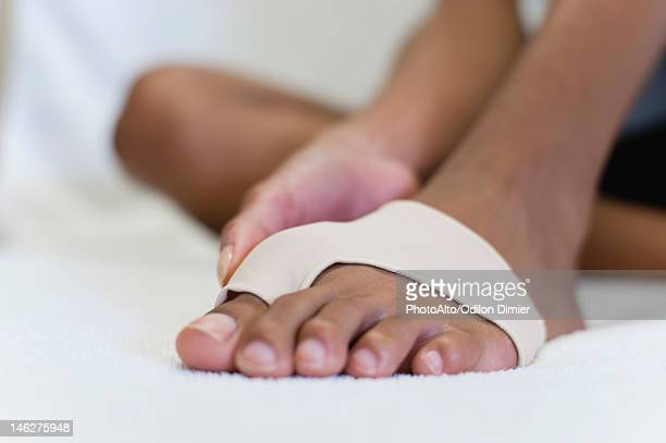 Woman's foot wrapped in brace for injured toe, low section