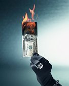 Woman's gloved and jeweled hand holding burning US hundred dollar bill