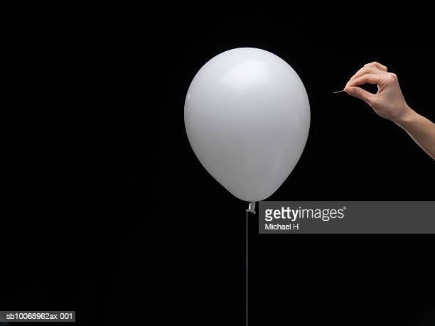 Woman's hand about to puncture balloon with pin