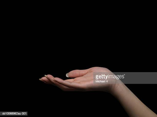 Woman's hand against black background