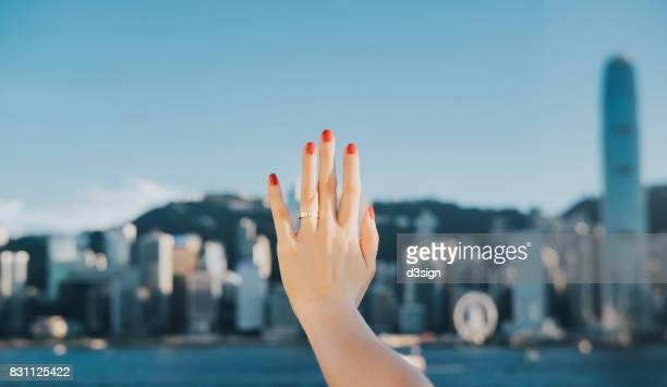 Woman's hand against iconic skyline of Hong Kong Victoria Harbour