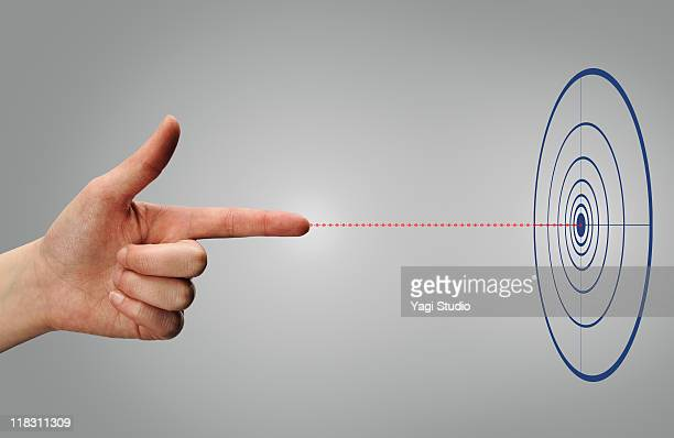 A woman's hand aims at a target.