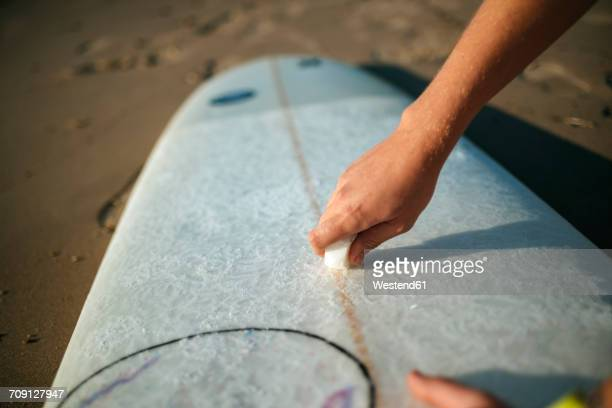 Womans hand applying paraffin on surfboard, close-up