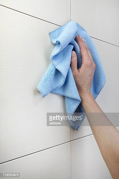 Woman's hand cleaning tile wall with blue rag