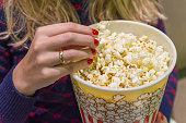 Woman's hand close up, picking up popcorn.