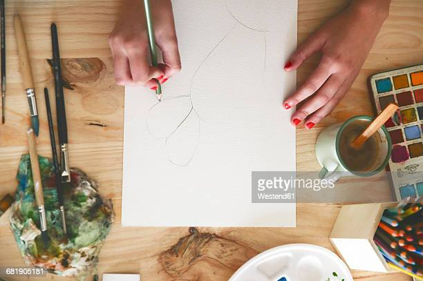 Womans hand drawing a cactus with green pencil on paper