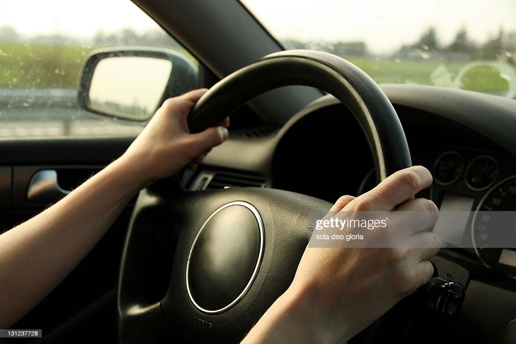 Woman's hand driving car : Stock Photo