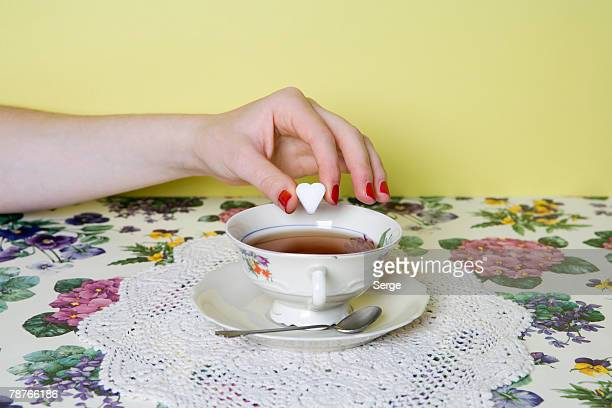 A woman's hand dropping a heart shaped sugar cube into a cup of tea