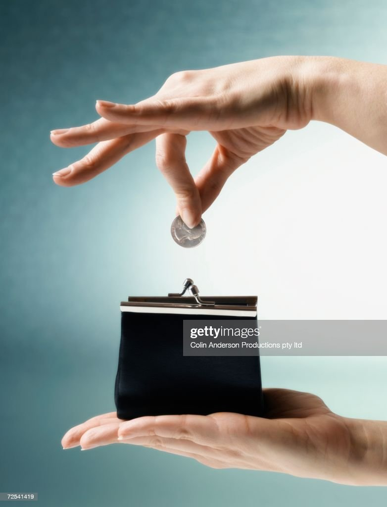 Woman's hand dropping coin into change purse : Stock Photo