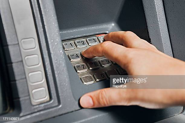 Woman's hand enters code on ATM keypad