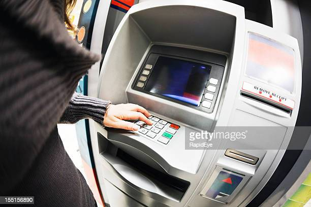 Woman's hand enters details on bank's ATM machine