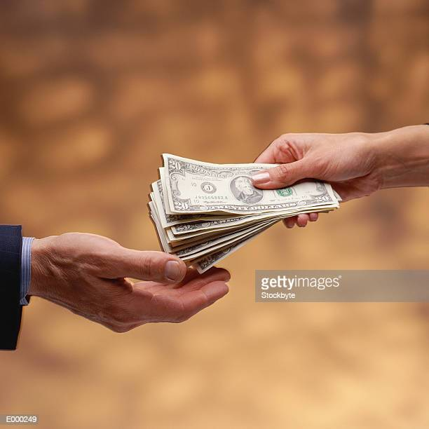 Woman's hand giving stack of US $20 bills to man's hand