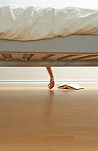Woman's hand hanging over bed, view from below bed, book on floor