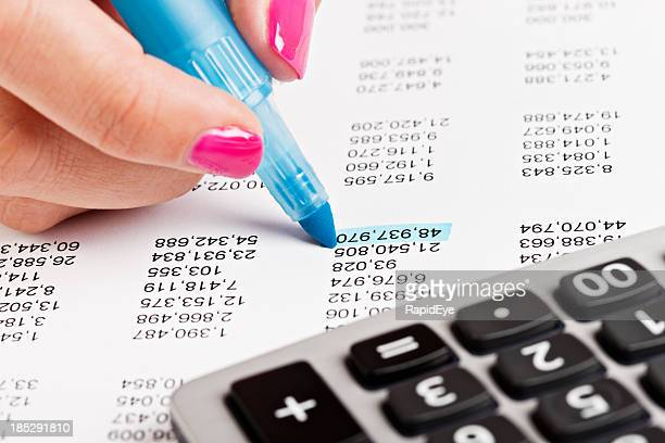 Woman's hand highlights figure on financial document in blue