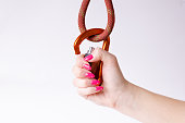 Woman´s hand holding a carabine on a rope. Climbing equipment isolated on a white background.